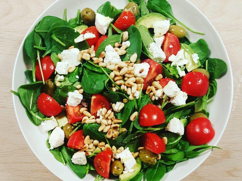 Salade van babyspinazie, geitenkaas, avocado en pijnboompitten